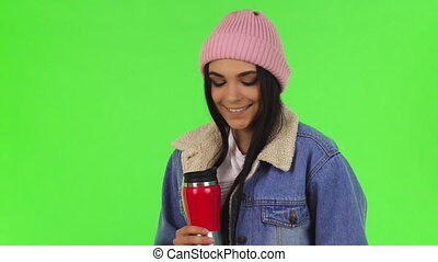 Gorgeous young woman wearing warm hat and jacket having tea
