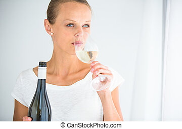 Gorgeous young woman with a glass of wine, smelling the lovely drink, savouring every sip
