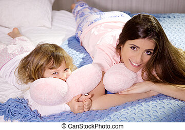 Gorgeous young woman with daughter hugging pink soft pillow heart in bed