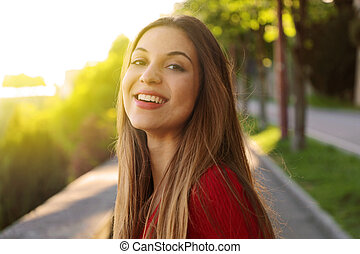 Gorgeous young woman with long hair turn the head and looking at camera when walking in the street