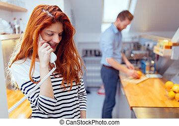 Gorgeus woman talking on phone in kitchen