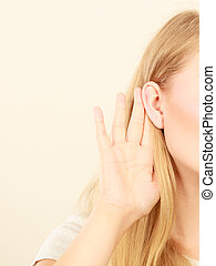 Woman putting hand ear to hear better