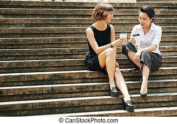 Gossiping businesswomen sitting on steps