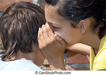 Gossiping - girl telling secret to boy closeup outdoor