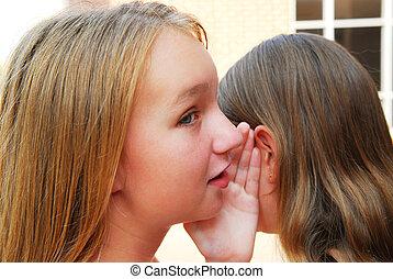 Gossiping - Two young teenage girls gossiping in school yard