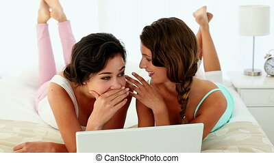 Gossiping young women lying on bed