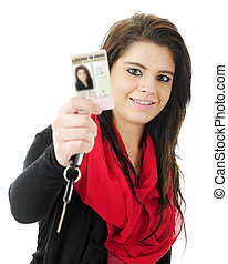 Close-up of a pretty teen girl happily holding up her new driver's license for the viewer to see, along with a car key. Focus on teen. On a white background.