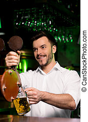 Got some beer? Cheerful young bartender pouring beer and ...
