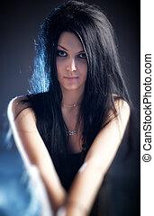 Goth woman portrait. On dark background.