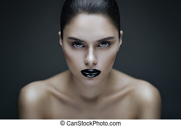 Fashion portrait of young brunette woman with black lips. Shallow depth of field