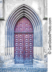 Gothic door into stone historic building.