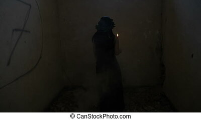 Gothic dressed vampire woman holding a candle turning around in a smoky abandoned house