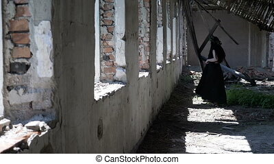 Gothic fairy looking by the ruined window in an abandoned...