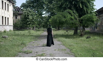 Gothic girl with long hair and black dress walking between old abandoned buildings