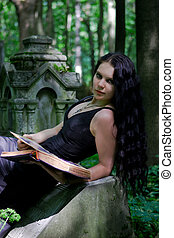 Gothic girl with old book posing on gravestone