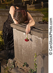 Gothic sorrow - Crying gothic girl leaning on a tombstone...