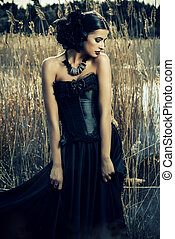 Beautiful brunette woman wearing long black dress and black headwear posing among the reeds. The old times, the Gothic style. Fashion.
