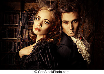 gothic times - Beautiful man and woman vampires dressed in...