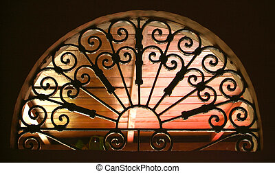 An old rusted window with a gothic pattern