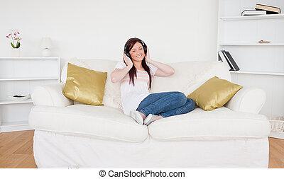 gott tittande, rödhårigt, kvinnlig, avlyssna musik, med, hörlurar, medan, sittande, på, a, soffa, in, den, vardagsrum