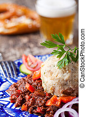 goulash with dumpling on a blue plate