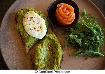 Gourmet appetizers salmon avocado spread toasts arugula plate top view