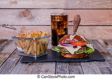 Gourmet cheeseburger with fries and drink