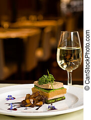 Gourmet dish and white wine, restaurant, copy space.
