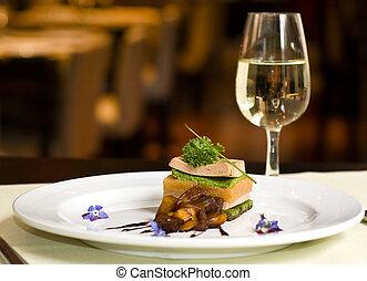 Gourmet dish and white wine, restaurant.