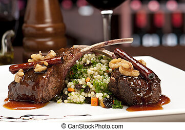 Close up of lamb chops with couscous and vegetables with a sauce of caramel, pepper and spices in a restaurant setting.
