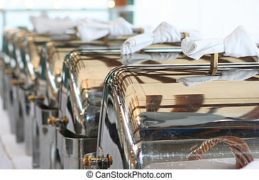 Gourmet - A line of silver serving trays blurring in the...