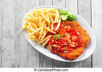 Gourmet Potato Fries and Saucy Escalope on Table