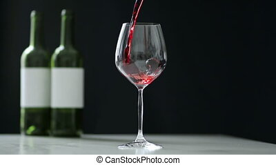 Gourmet Wine - Red wine being poured from bottle to...