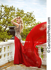 Gown. Beautiful sexy young woman model in elegant mermaid blowing red dress posing on the balcony with park view.