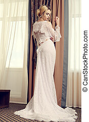Full length portrait of a magnificent young woman in elegant long dress. Luxurious apartments. Wedding fashion.