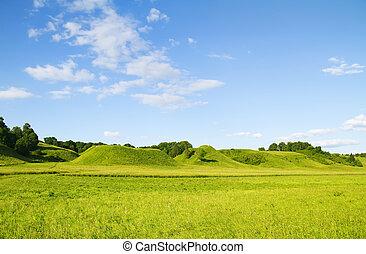 grönt kulle, blå, mulen himmel