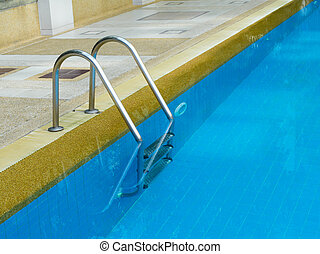 Grab bars ladder in swimming pool in daylight
