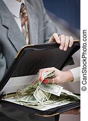 Grabbing money - female hand grabbing cash dollars from a...