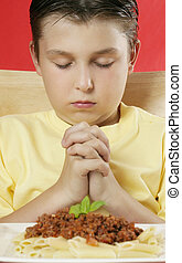 Grace - A boy with hands clasped giving thanks before a meal