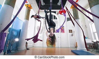 Grace women circling on the aerial hoop and silk in a studio
