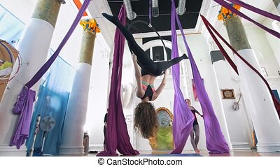 Grace women makes a gymnastic elements on the aerial hoop and silk in a studio