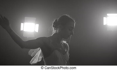 graceful ballerina dancing on the stage. Smoke, fog, ballet dancer in white tutu, girl in pointe, whirls around in the dark with purple light on the black background