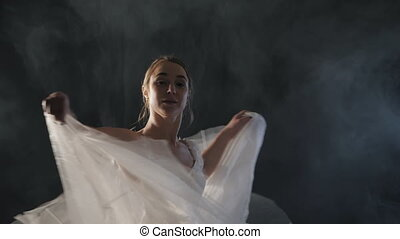 graceful ballerina doing a workout in the classroom. Smoke, fog, ballet dancer in white tutu, girl in pointe, whirls around in the dark with light on the black background, 4k