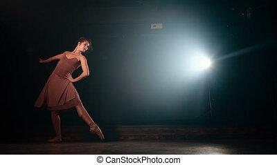 Graceful ballerina in beige dress dancing elements of classical or modern ballet in dark with floodlight backlight. Smoke on black background. Art concept. 4k