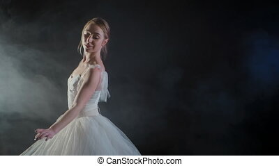 graceful ballerina in white dress dancing elements of classical or modern ballet in the dark with light and smoke on the black background, slow motion