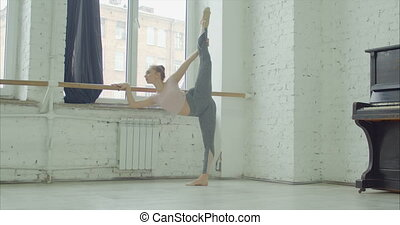Graceful ballerina practicing standing split - Graceful...