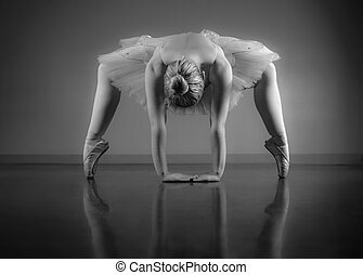 Graceful ballerina warming up in black and white in the...