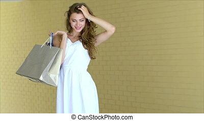Graceful beautiful girl posing with trendy shopping while shopping