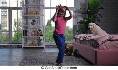 Graceful child dancing for puppy sitting on bed - Cute...
