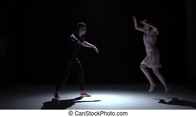 Graceful contemporary dance of couple dancers on black, shadow, slow motion
